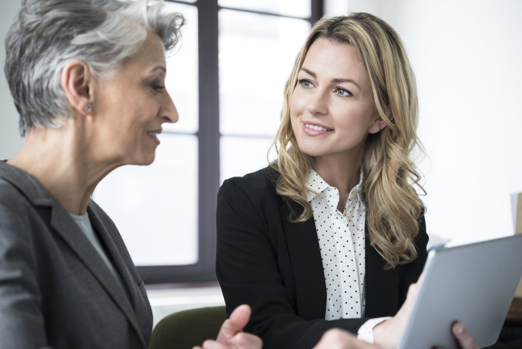 Attractive mid adult businesswoman with long blonde hair talking to mature colleague with short grey hair in office.