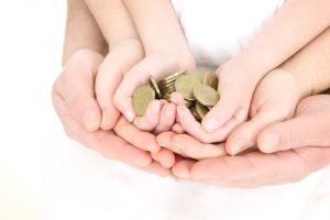 """A family's hands (child, mother and father) holding a handful of gold coins."""
