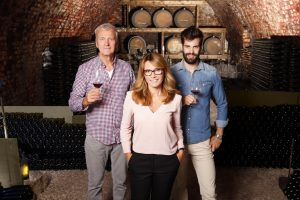 Portrait of multigenerational winery owner family standing at wine cellar. Senior winemaker and young sommelier standing at background and holding in hands a glass of red wine while middle age businesswoman looking at camera and smiling. Small business.